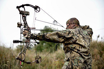 A hunter in green camouflage clothing  stands in tall green and yellow grass aiming a compound bow