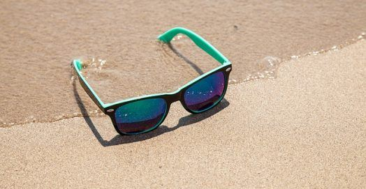 best sunglasses for men lying on the beach sand