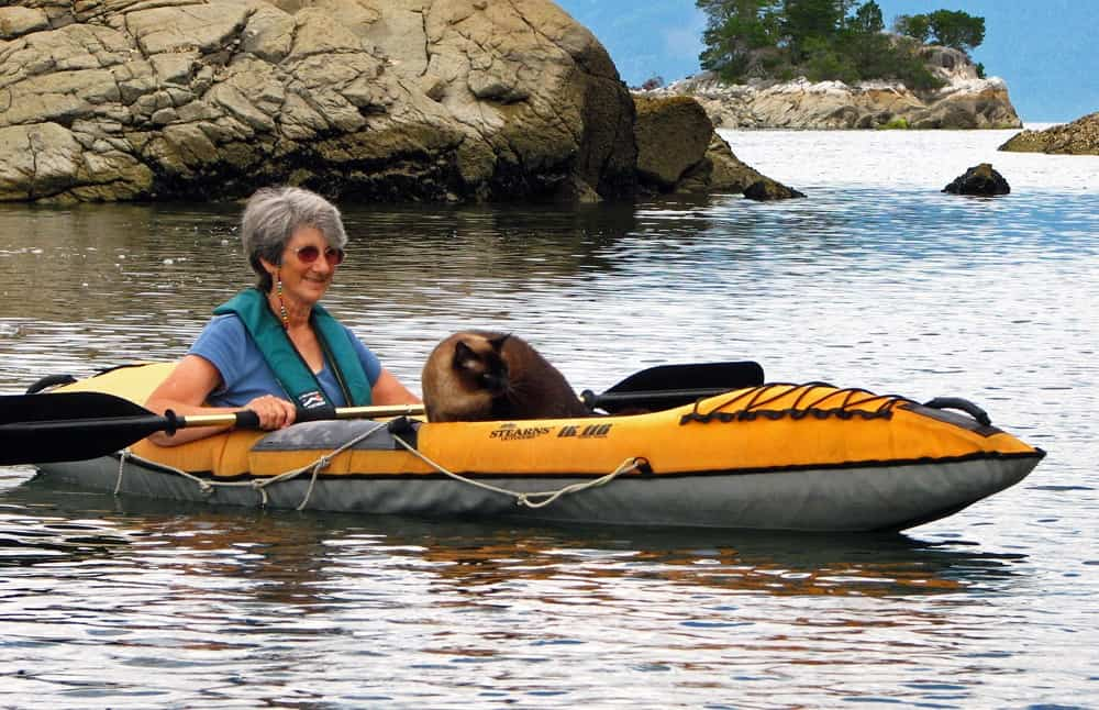 granny enjoying herself paddling the best inflatable kayak with her cute cat