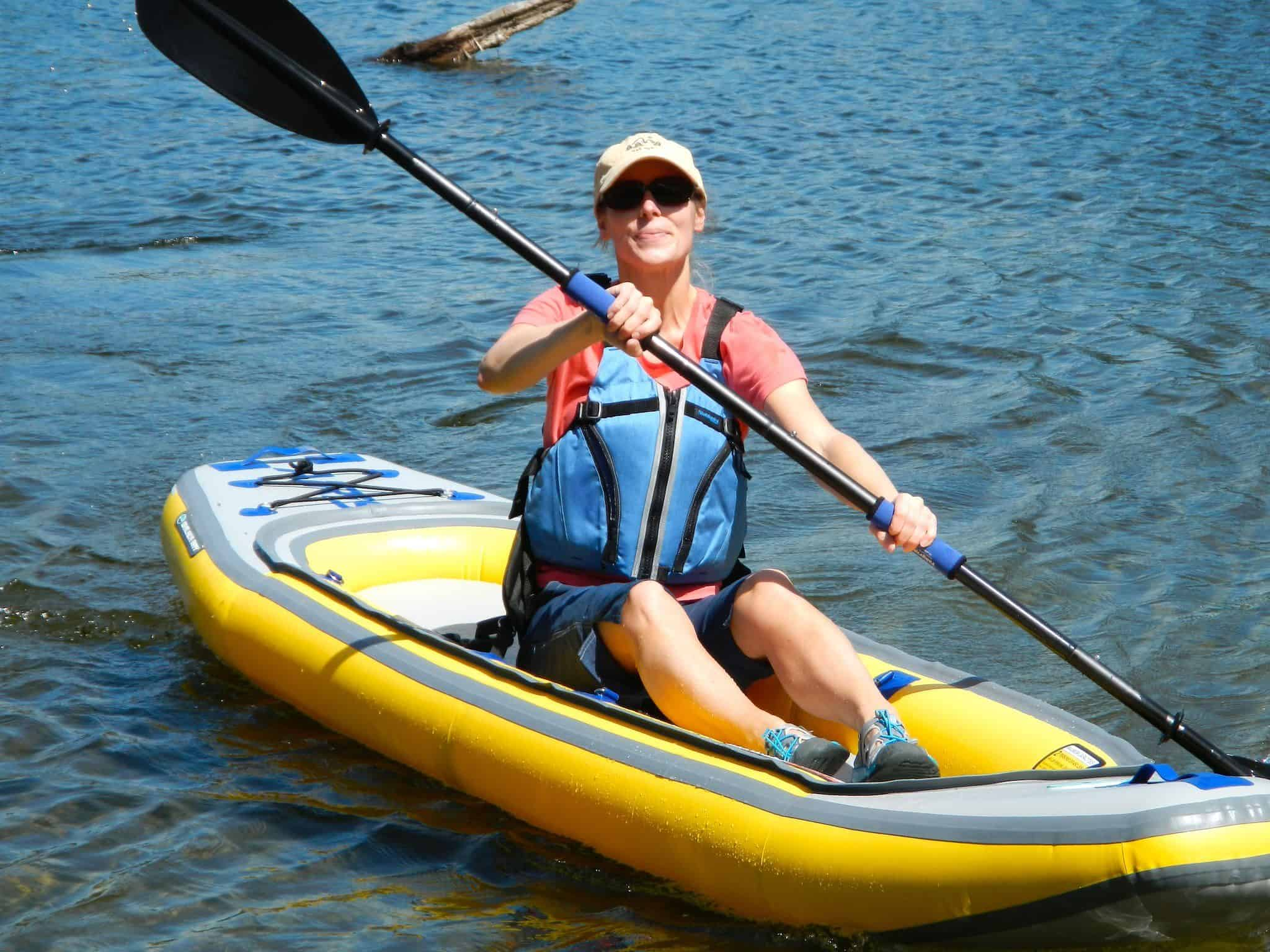 Girl wearing a life vest was paddling the best inflatable kayak