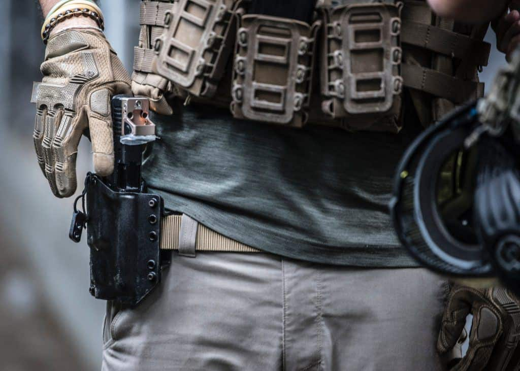 a person putting his handgun on his holster belt