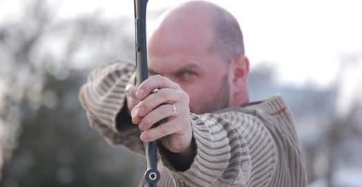 man shooting head arrow